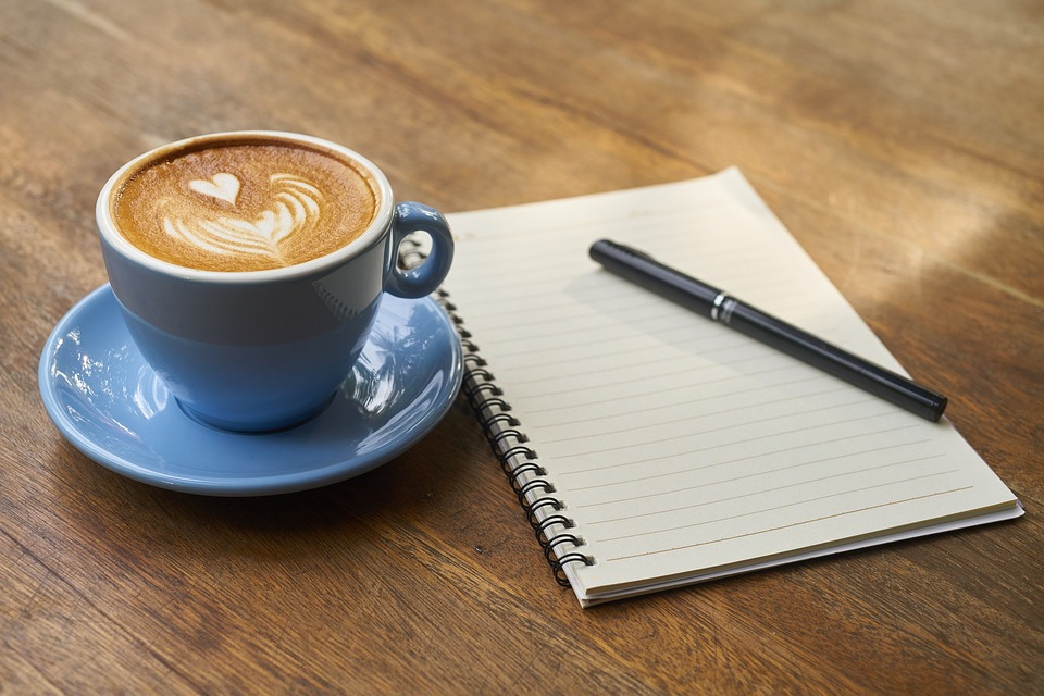 Photo of coffee cup and writing pad